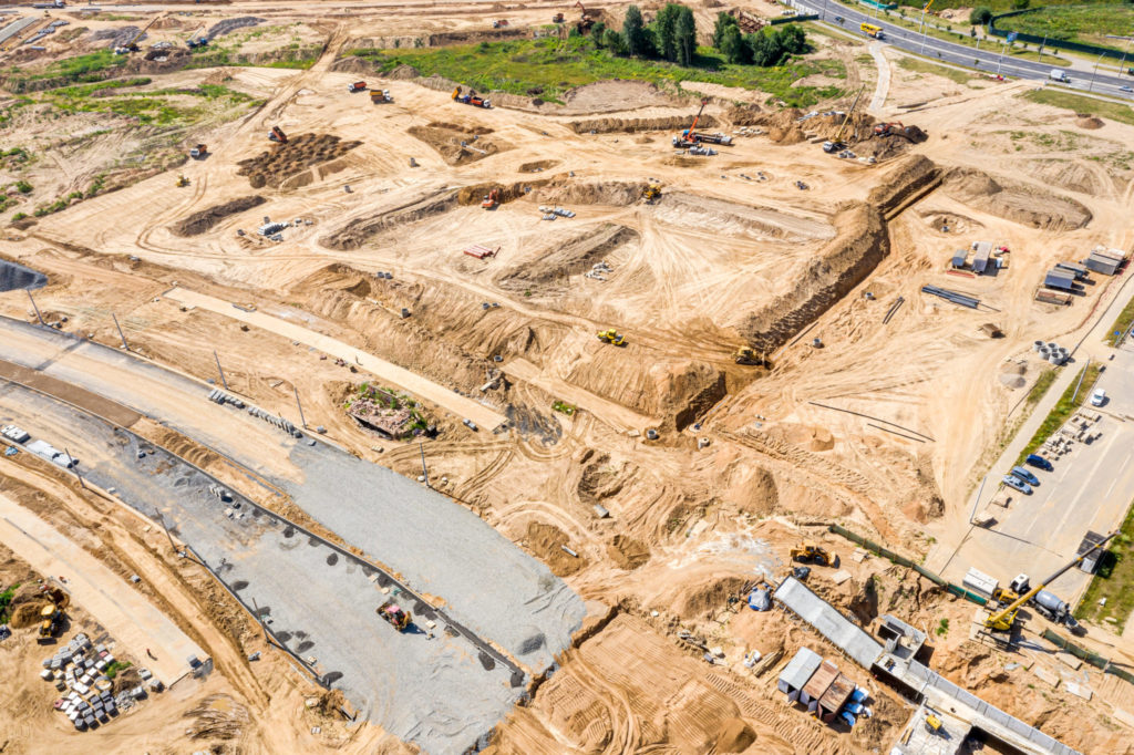 construction of new road, aerial top view. industrial machinery working at construction site
